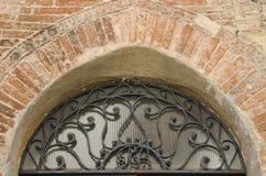 Tegelsten och järn ovanför dörr i Montepulciano, Italien Arkivfoto