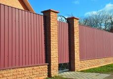 Tegelsten- och metallstaket med dörren och porten Fäktningkonstruktion fotografering för bildbyråer