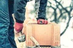Tegelstenar för fixande för murarekonstruktionstekniker och byggnadsväggar på det nya huset på en kall vinterdag Royaltyfria Bilder