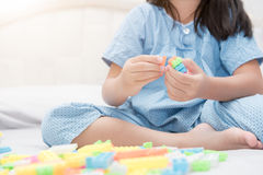 Tegelstenar för flickalekkvarter på säng, utbildning Royaltyfria Bilder