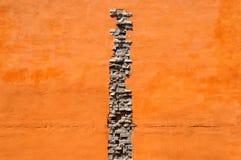 tegelstenar knäcker den orange väggen Arkivfoto
