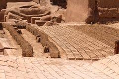 Tegelstenar som bakas i solen i staden av Rayen, Iran arkivfoton