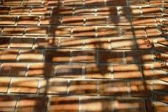 Tegelstenbana med skugga fr?n solljus arkivfoto