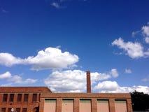 Tegelstenbyggnad med fabriksskorsten och blå molnig himmel Royaltyfri Foto
