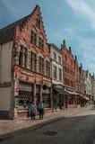 Tegelstenbyggnad, shoppar och folk i gata av Bruges Arkivbilder
