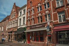 Tegelstenbyggnad, shoppar och folk i gata av Bruges Royaltyfri Fotografi
