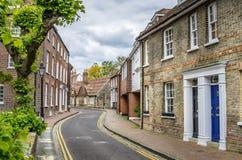 Tegelstenbyggnader längs en smal gata i England Arkivbild