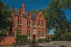 Tegelstenfasad av det gamla huset, träd och cyklar i Bruges Arkivfoton