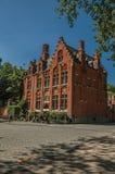 Tegelstenfasad av det gamla huset, träd och cyklar i Bruges Arkivfoto