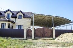 Tegelstenhus med ett staket och portar En stor markis med en stålram Sikt av ett nytt byggt-upp staket och ett hus som göras av t Arkivfoto