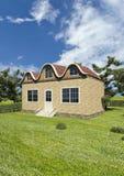 Tegelstenhus med trees och lawn arkivfoto