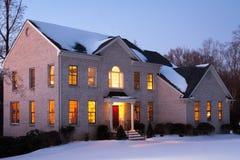 Tegelstenhus på skymningen med Snow Arkivfoton