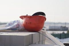 tegelstenkonstruktion som utomhus lägger lokalen Orange hjälm för head skydd Arkivfoto