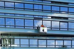 tegelstenkonstruktion som utomhus lägger lokalen Wokers rengöring glasväggen av ny kontorsbyggnad Vilnius Litauen - Juni 29, 2016 Royaltyfri Fotografi