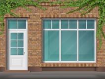 Tegelstenlagerframdel med det stora fönstret och murgrönan Arkivfoton
