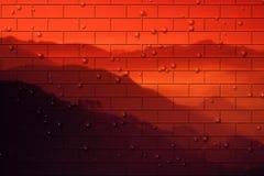 tegelstenliggande över den röda väggen Arkivbild