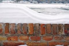 Tegelstenstaket som täckas med snö, vänster sida arkivbilder