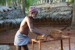 Tegelstentillverkaren är upptagen med att använda för danandetegelsten som är claysand Arkivfoto