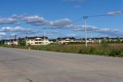 Tegelstentvå-våning stugor på gatan nära stadsutkanten Två-våning hus på gatan, blå himmel royaltyfria bilder