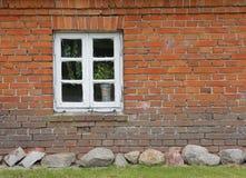 Tegelstenvägg av det gamla huset med trämuntinfönstret Arkivbilder