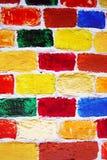 Tegelstenvägg av många färgrika målade tegelstenar Arkivfoton