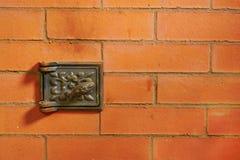 Tegelstenvägg med den lilla metalldörren Arkivfoto