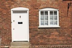 Tegelstenvägg med den vita dörren och fönstret Royaltyfri Fotografi