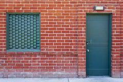 Tegelstenvägg med en grön metalldörr royaltyfri bild