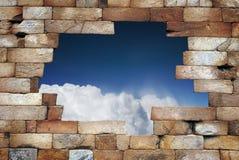 Tegelstenvägg med hålet ändå himlen Arkivbild