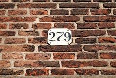 Tegelstenvägg med husnummer Arkivbild
