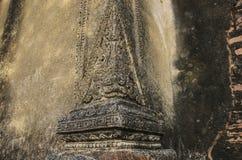 Tegelstenvägg med lövsågsarbetet i form av huvudet av ett mytiskt c royaltyfri foto