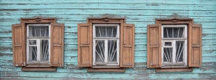 Tegelstenvägg med många träfönster arkivfoto