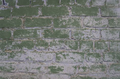 Tegelstenvägg med restna av målarfärg royaltyfria foton