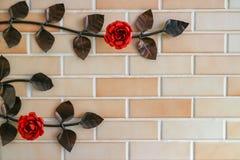 Tegelstenvägg med rosfilialen Arkivfoto