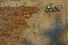 Tegelstenvägg med skada och siren Arkivbild