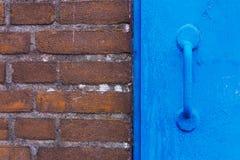Tegelstenvägg och blåttdörr Fotografering för Bildbyråer
