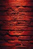 Tegelstenvägg och rött ljus på natten Royaltyfria Bilder