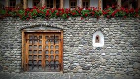 Tegelstenvägg, röda blommor, fönster som är traditionella Arkivfoto