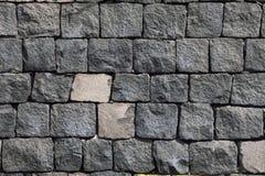 Tegelstenvägg som göras av lavastenen detaljerad verklig sten för bakgrund mycket Arkivbilder