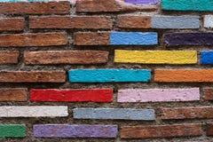 Tegelstenvägg som målas in i ljusa färger arkivfoton