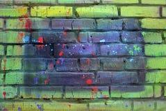 Tegelstenvägg som målas med mångfärgad målarfärg arkivfoton