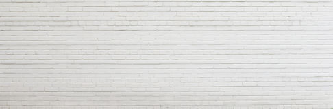 Tegelstenvägg som målas med vit målarfärg Arkivbild