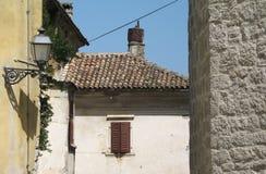 Tegelstenväggar av den gamla gatan av en liten stad med en streetlight, Istria, Kroatien royaltyfri foto