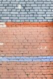 Tegelstenväggen målas inte fullständigt med orange målarfärg En ovanlig bakgrund Texturen av stenmurverket Arkivfoton