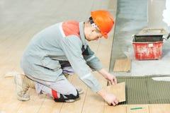 Tegelzetter aan het industriële vloer het betegelen vernieuwingswerk Royalty-vrije Stock Foto's