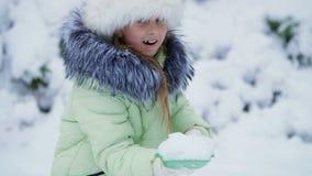 Tegen de achtergrond van het de winterlandschap, speelt het meisje pret in de werf met sneeuw, werpt, bestrooit de sneeuw stock footage