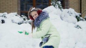 Tegen de achtergrond van het de winterlandschap, speelt het meisje pret in de werf met sneeuw, werpt, bestrooit de sneeuw stock videobeelden