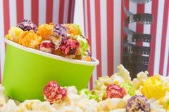 Tegen de achtergrond van rode en witte streep-glazen, kleurrijke die popcorn, door gezouten korrels wordt omringd stock foto