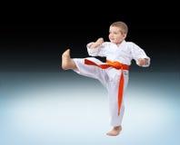 Tegen de achtergrondgradiënt slaat de atleet in karategi het schoppen stock fotografie