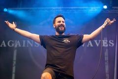 Tegen de band van de Golvenmuziek presteer in overleg bij de muziekfestival van het Download zware metaal stock foto